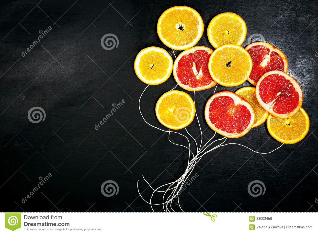 Food Art. Fruit slices on a dark Chalkboard Background with strings. Balloons from fruit slices. Healthy life, detox concept.