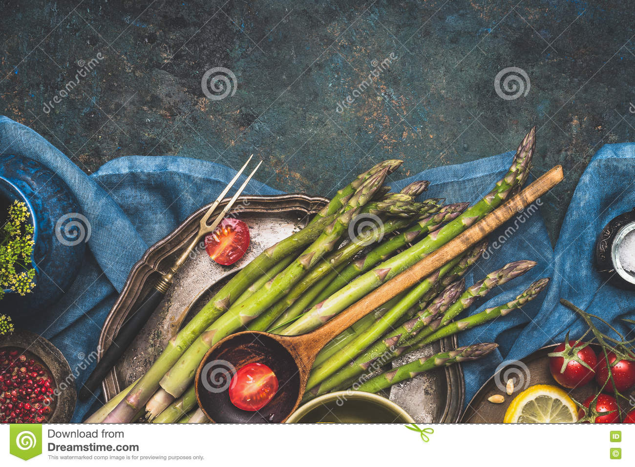 Food border with green asparagus, tomatoes,lemon and other ingredients for tasty asparagus cooking. Green asparagus preparation on
