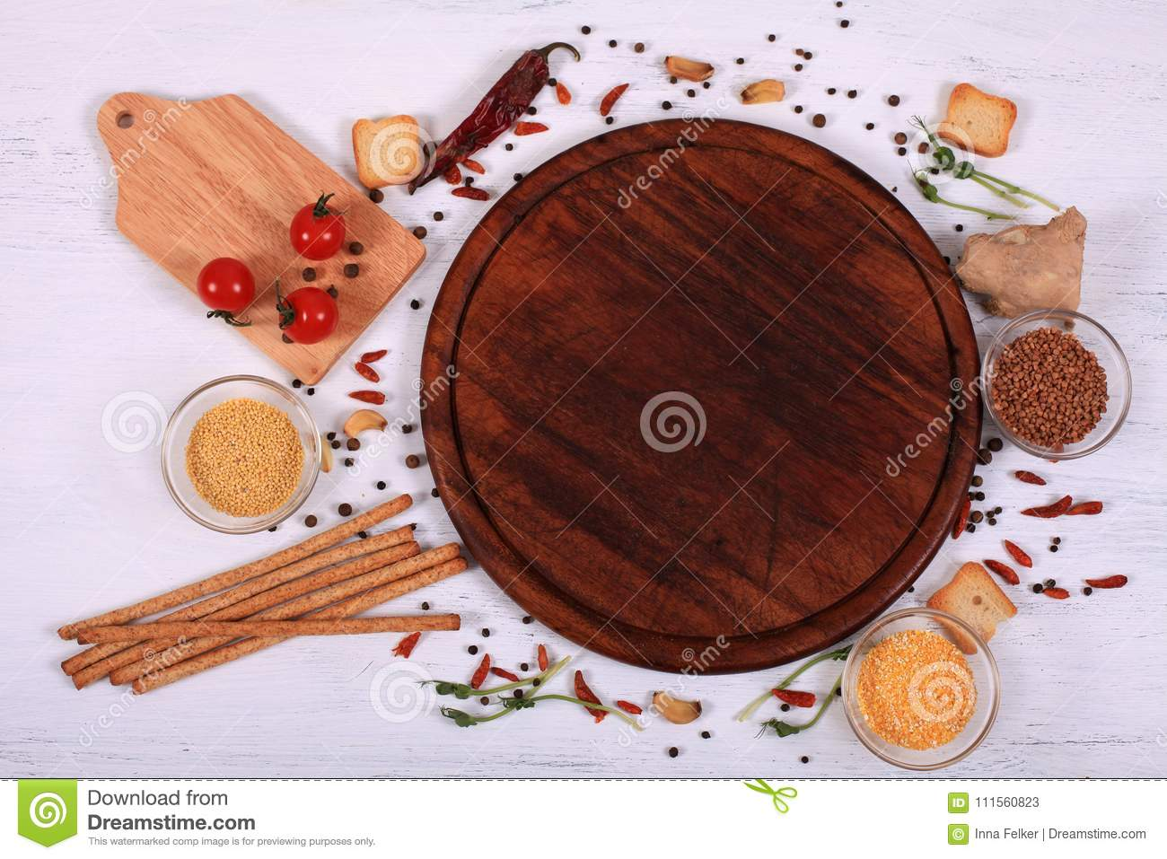 Food frame around brown round cutting board on white wooden table.