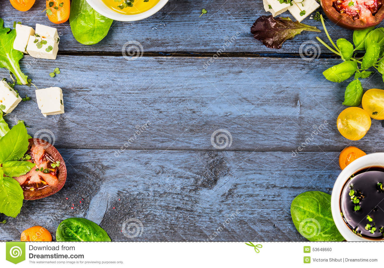 Food frame with salad ingredients: oil, vinegar, tomatoes, basil and cheese on blue rustic wooden background