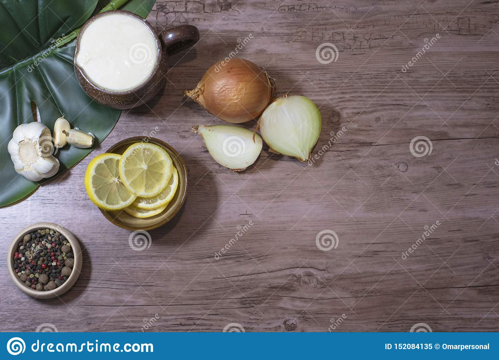 Food ingredients lemon slices onion yogurt garlic spices on a wooden table with a space in the right for written