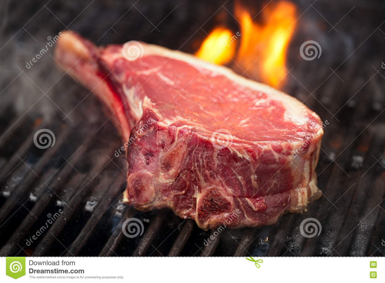 Food meat - beef steak on bbq barbecue grill with flame