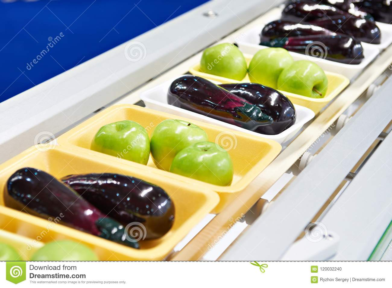 Food products apples and eggplant in plastic pack on conveyor