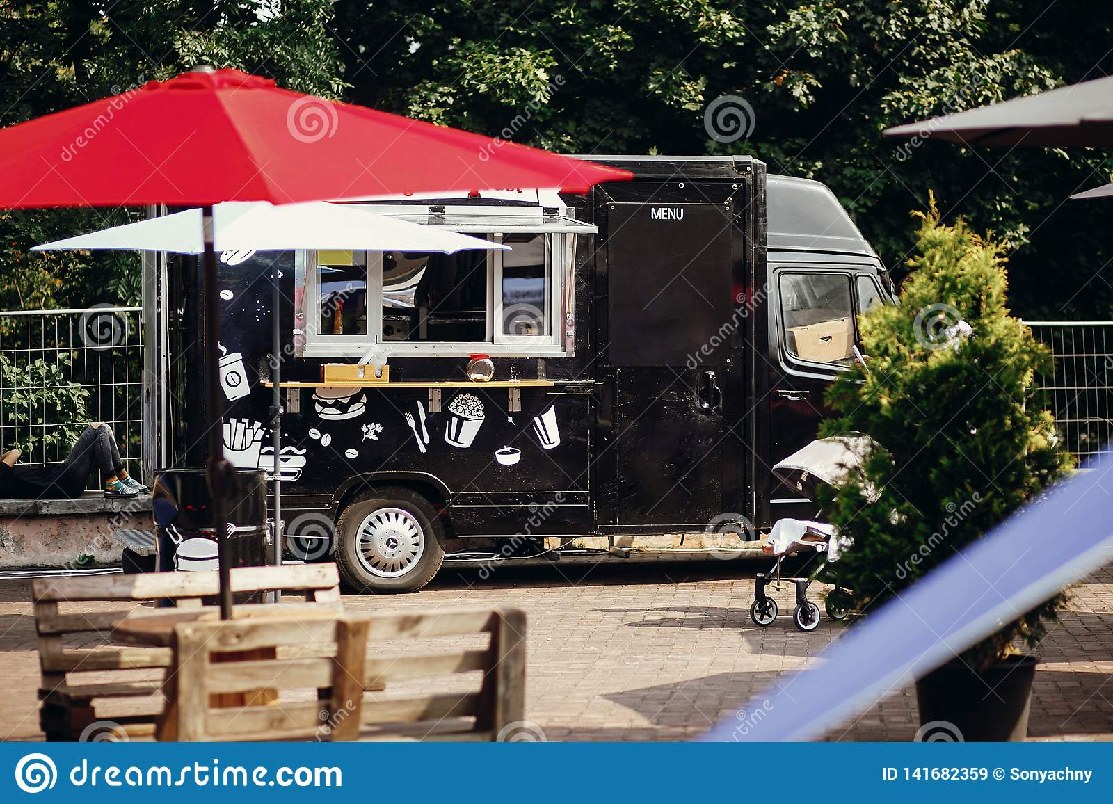 Food van truck. Stylish black mobile food truck with burgers and asian food at street food festival. Summer eating market in the