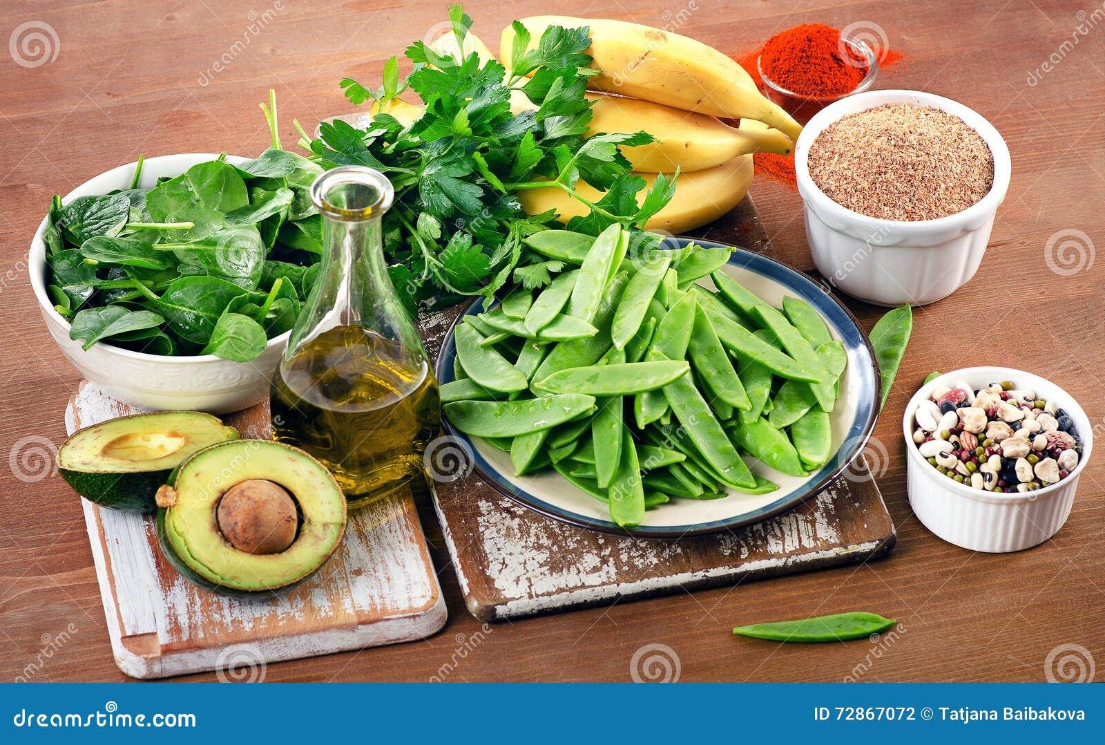 Foods högt i vitamin K på ett träbräde äta som är sunt