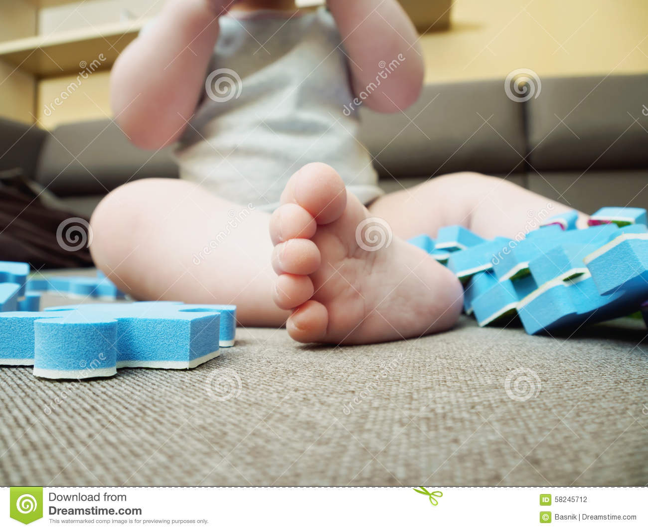 foot of baby with puzzle pieces on sofa in the living room at home stock photo image 58245712. Black Bedroom Furniture Sets. Home Design Ideas
