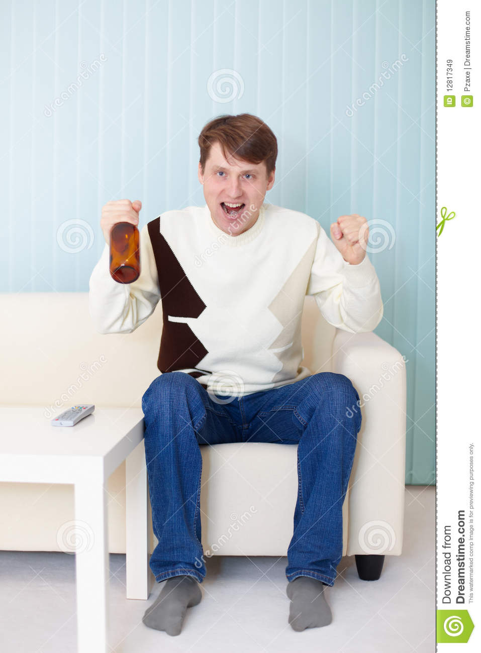 Football Fan Sitting On Sofa With Tv And Beer Stock Image