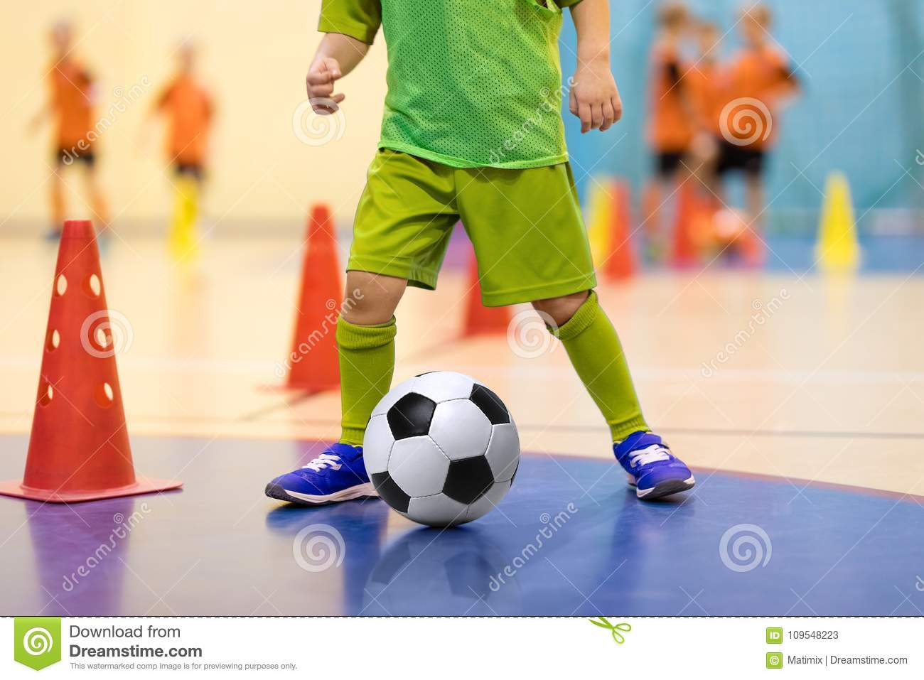 29d49a791 Football futsal training for children. Soccer training dribbling cone  drill. Indoor soccer young player with a soccer ball in a sports hall.