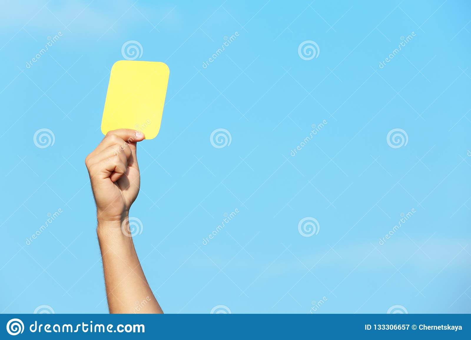 Football referee showing yellow card against blue sky