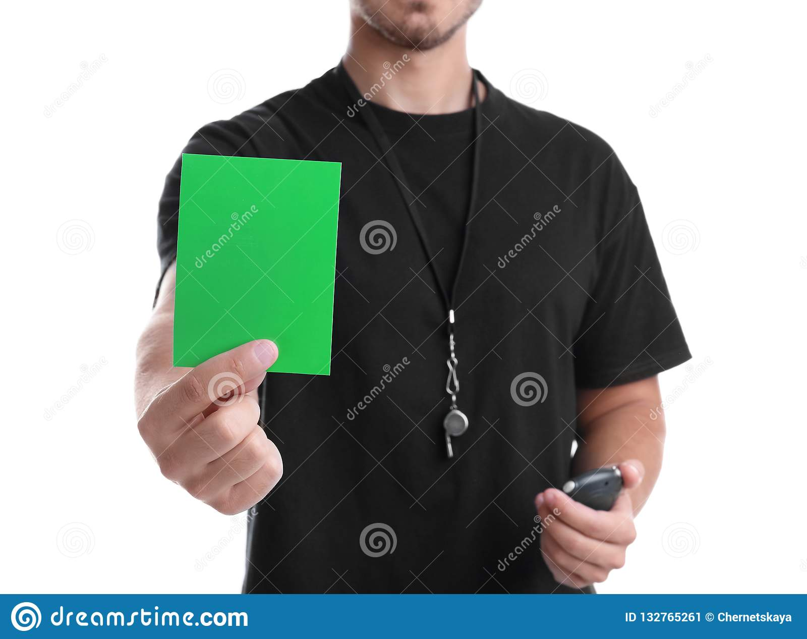 Football referee with stopwatch and whistle holding green card on white background