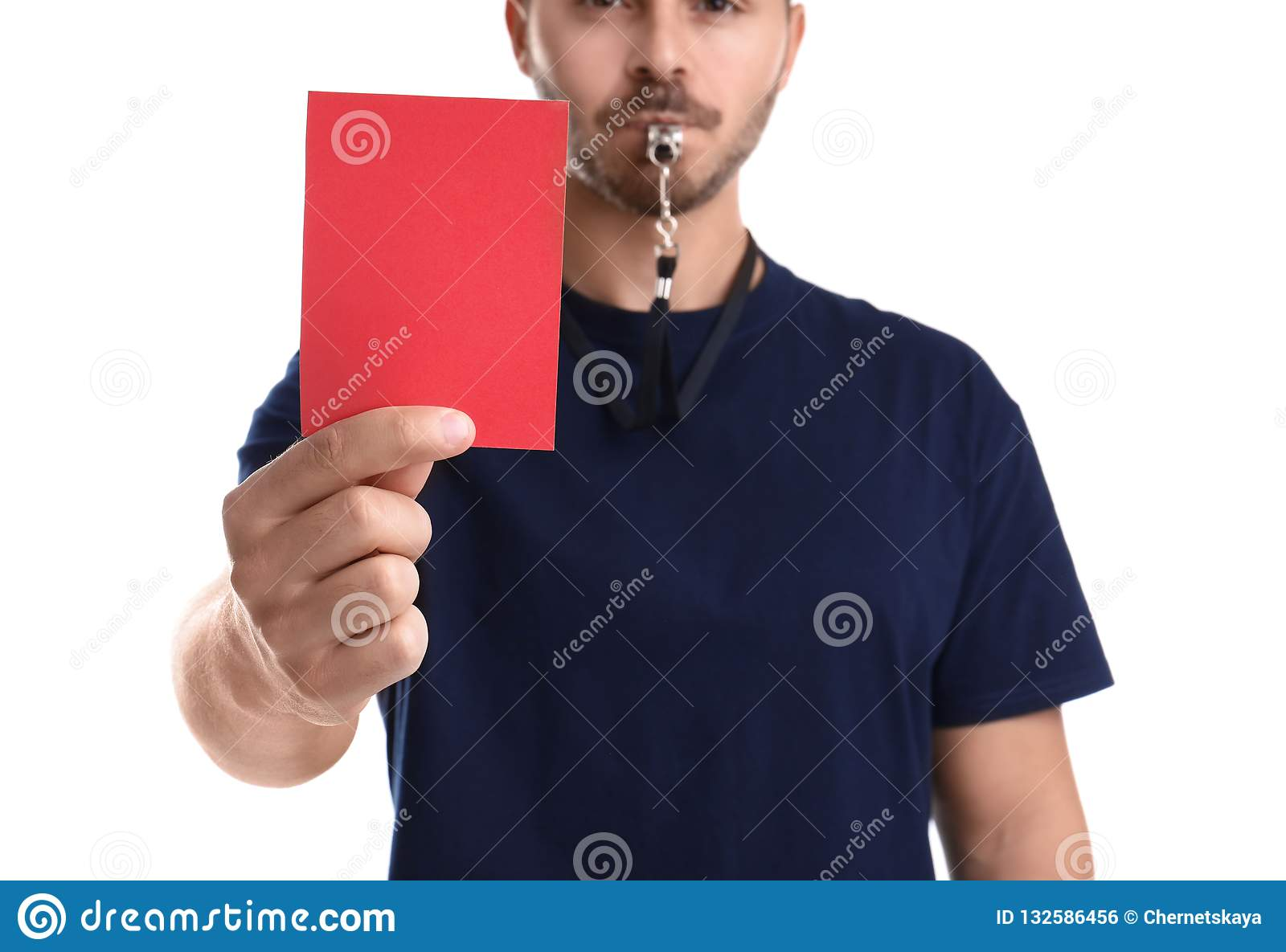 Football referee with whistle holding red card on white background