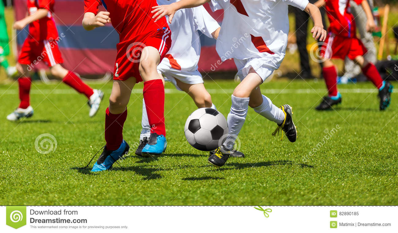 Football Soccer Kick. Soccer Players Duel. Children Playing Football Game on Sports Field. Boys Play Soccer Match on Green Grass