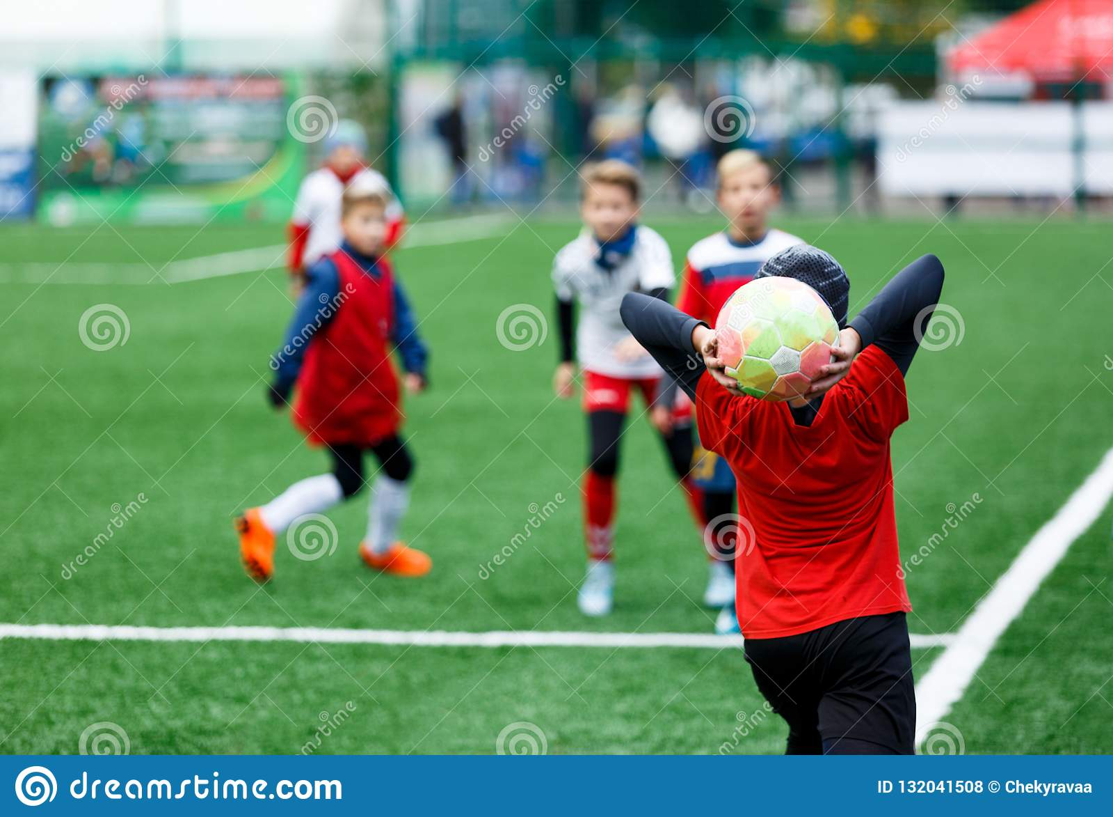 Football teams - boys in red, blue, white uniform play soccer on the green field. boys dribbling. dribbling skills.