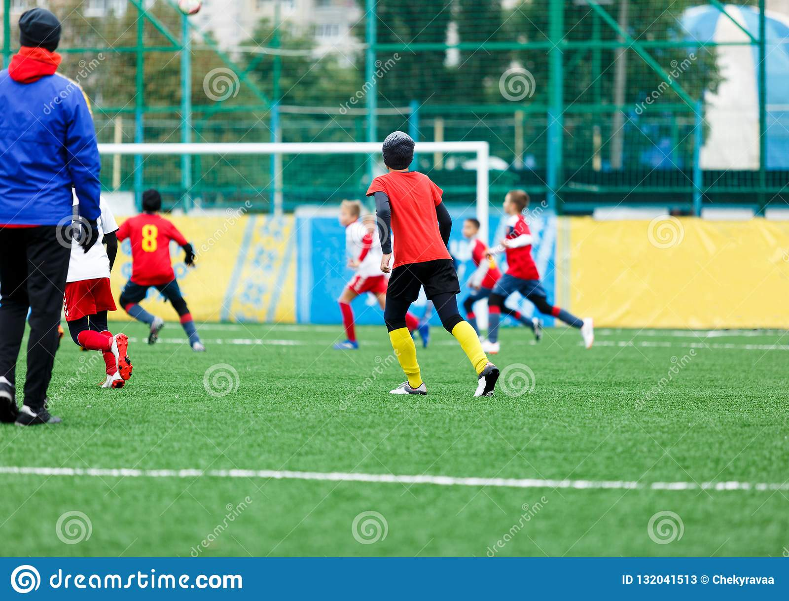 Football teams - boys in red, blue, white uniform play soccer on the green field. boys dribbling. dribbling skills. Team game