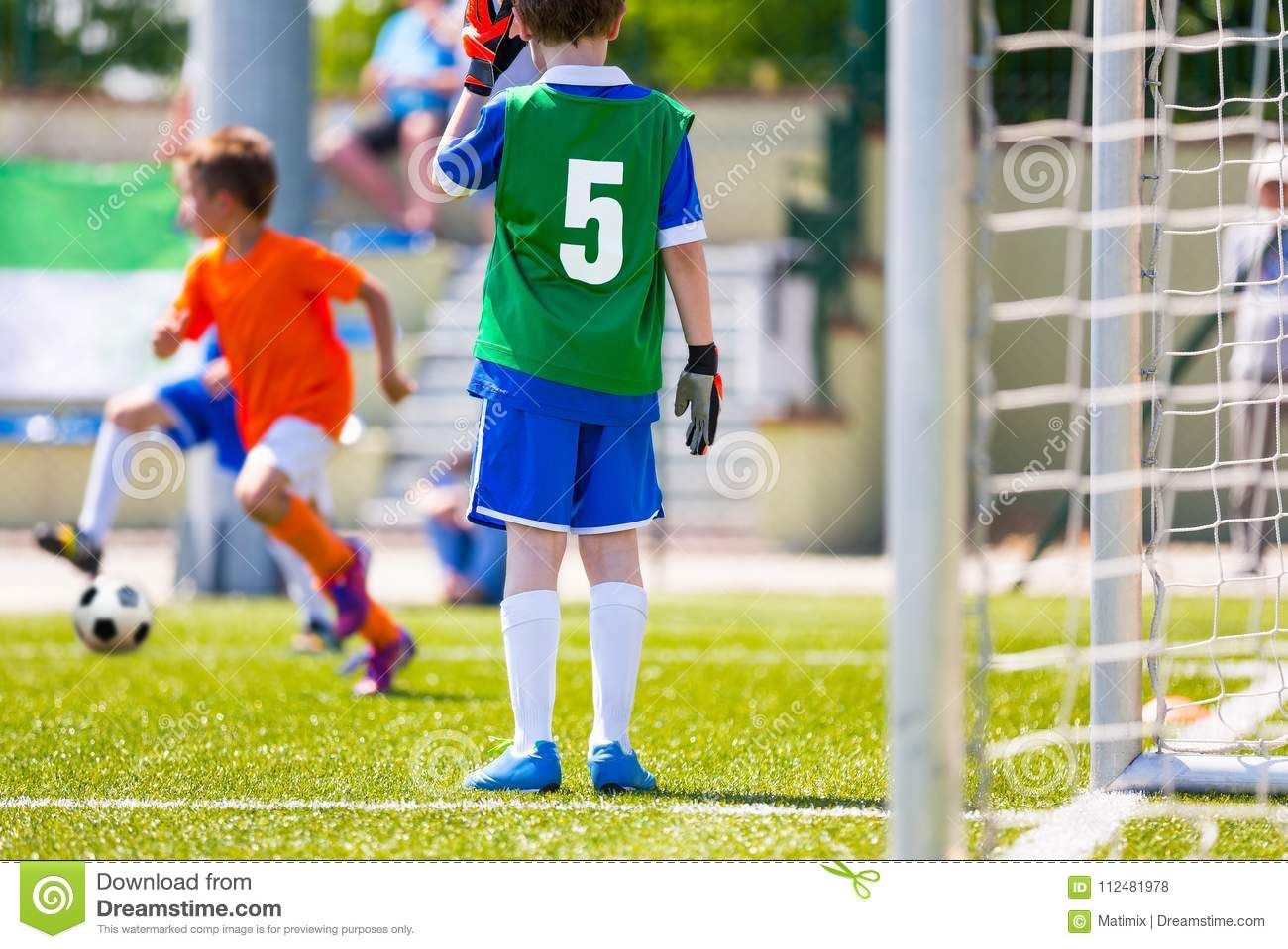 Football Training Game for Kids. Young Boy as a Football Goalkeeper Standing in a Goal. Soccer Players Running After the Ball