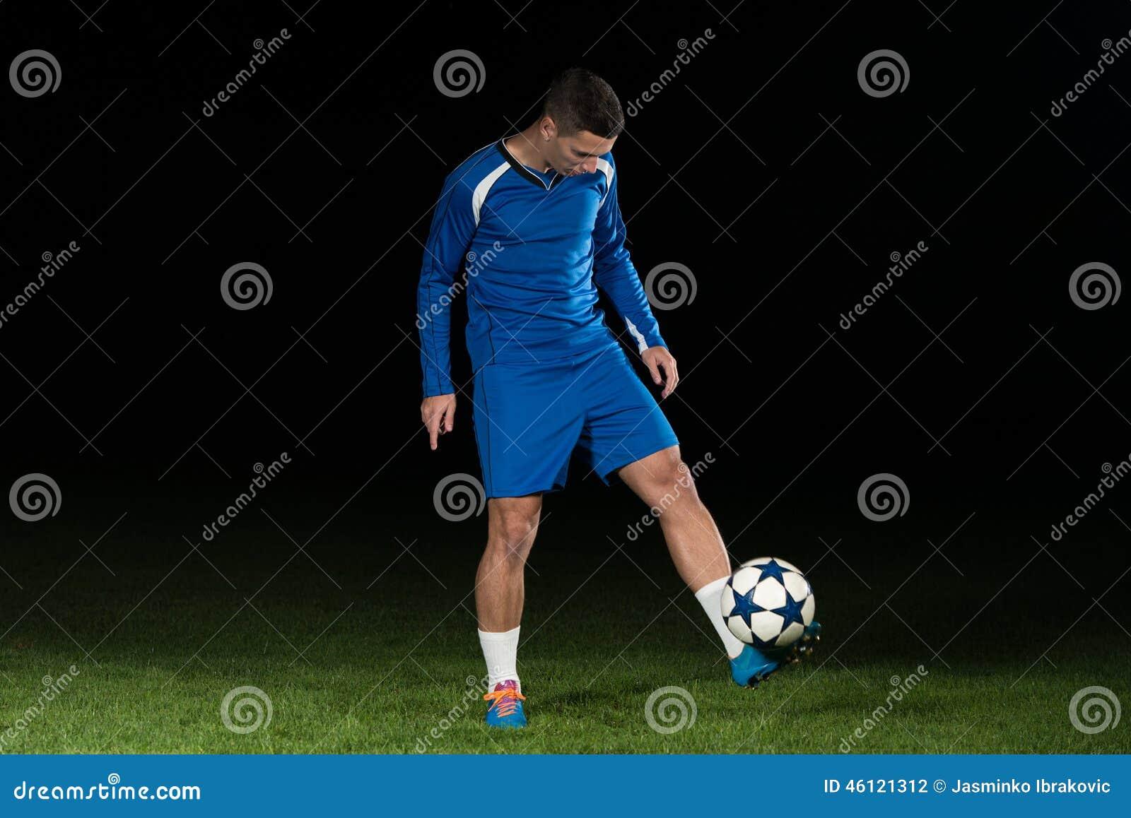 Footballeur professionnel donnant un coup de pied la boule d isolement sur le noir