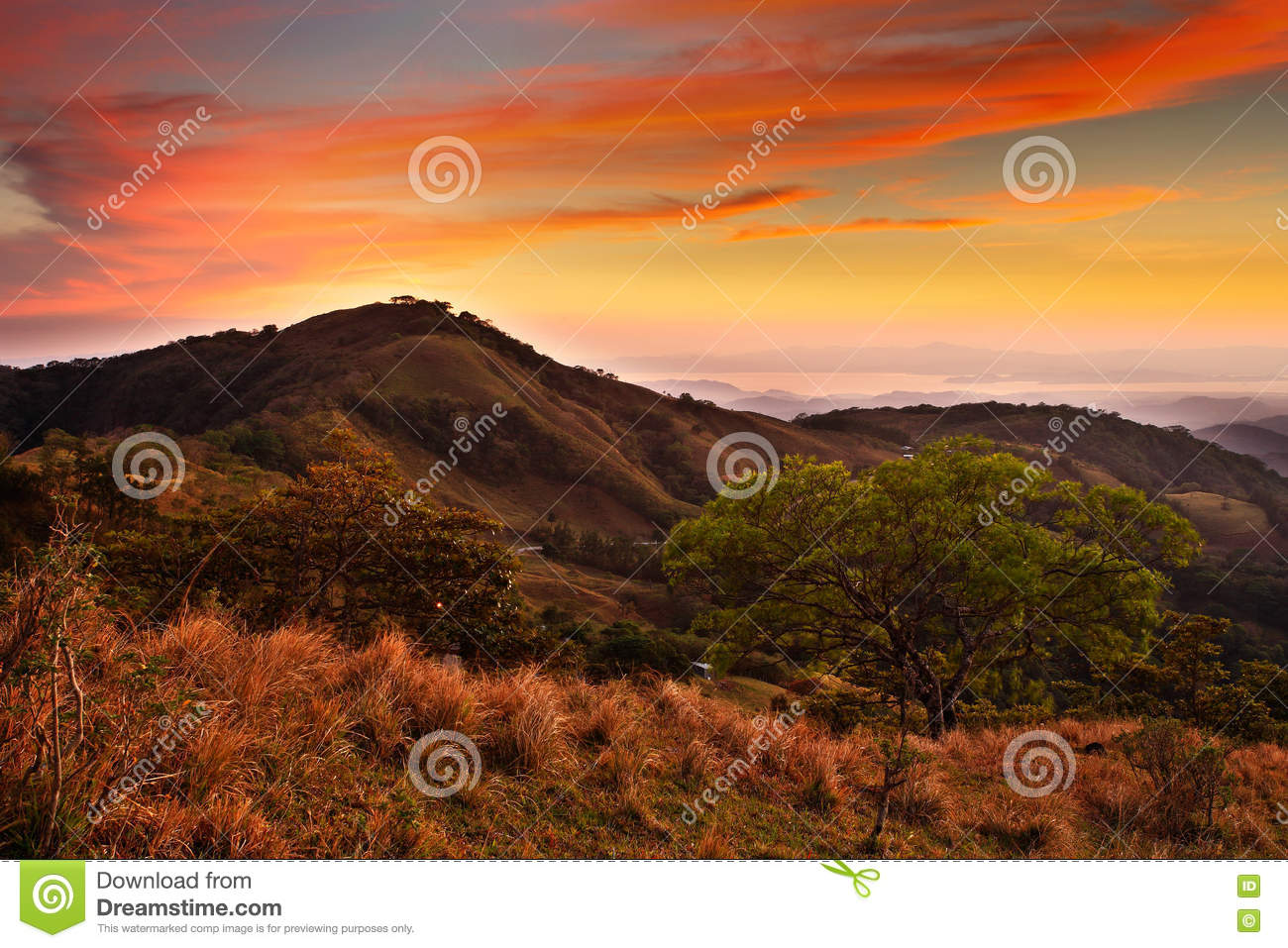 Foothills of Monteverde Cloud Forest Reserve, Costa Rica. Tropic mountains after sunset. Hills with beautiful orange sky with