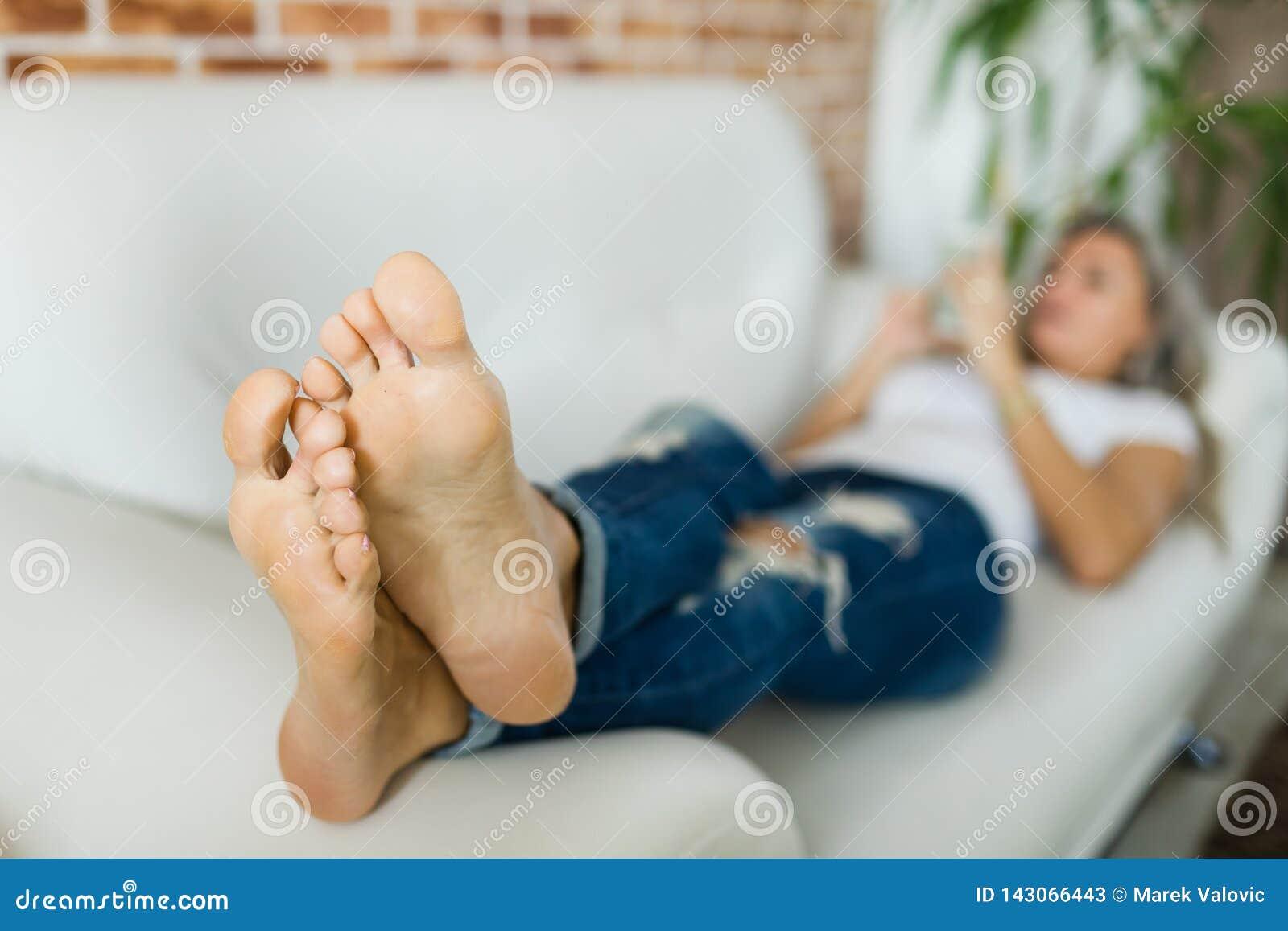 Foots młoda kobieta w cajgach używać mądrze telefonu lying on the beach na białej kanapie