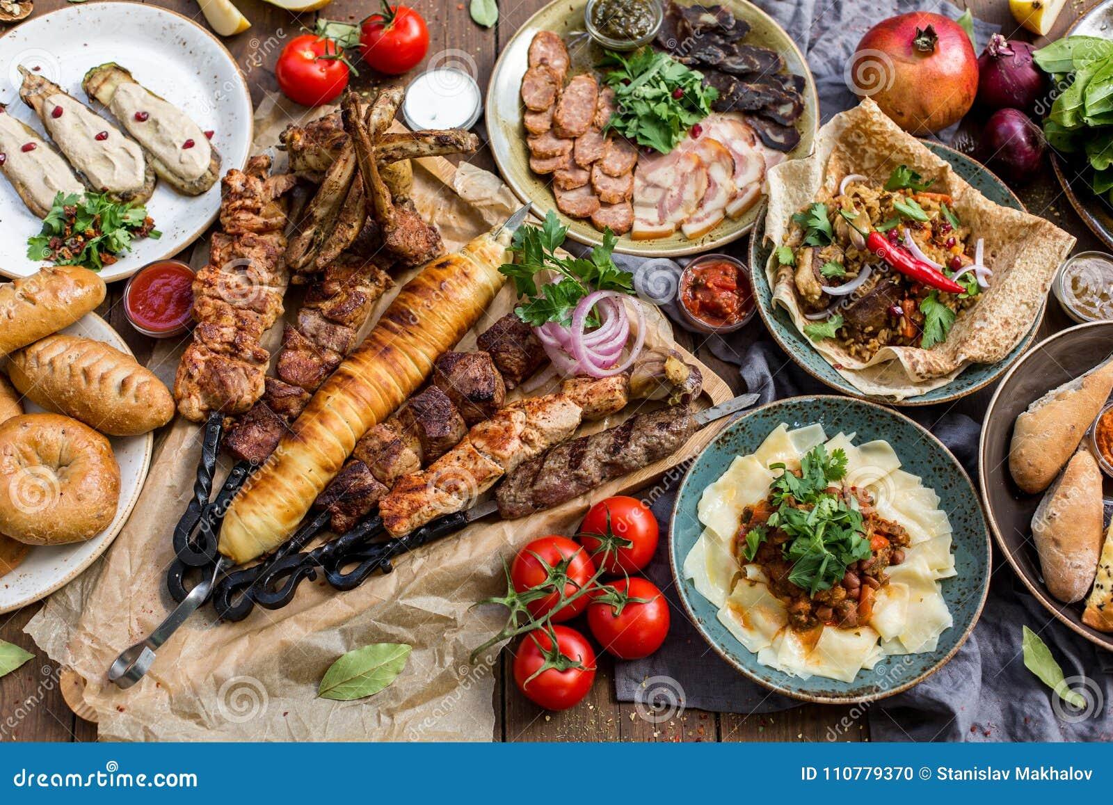 Fora conceito do alimento Bife assado apetitoso, salsichas e vegetais grelhados em uma tabela de piquenique de madeira