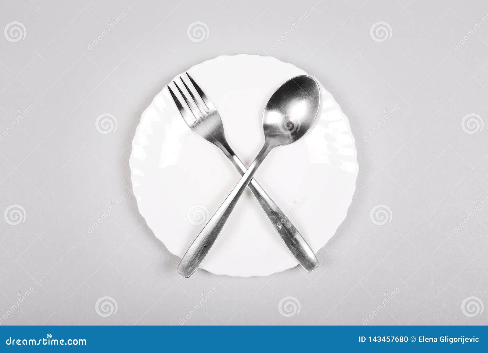 Forchetta e cucchiaio su un piatto bianco vuoto su fondo grigio