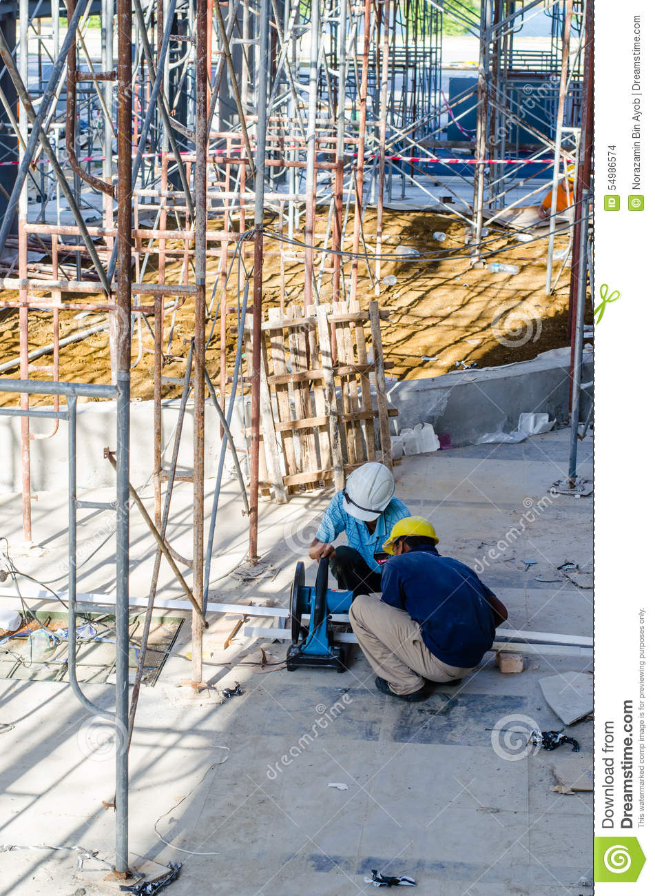 Foreign workers cutting construction material