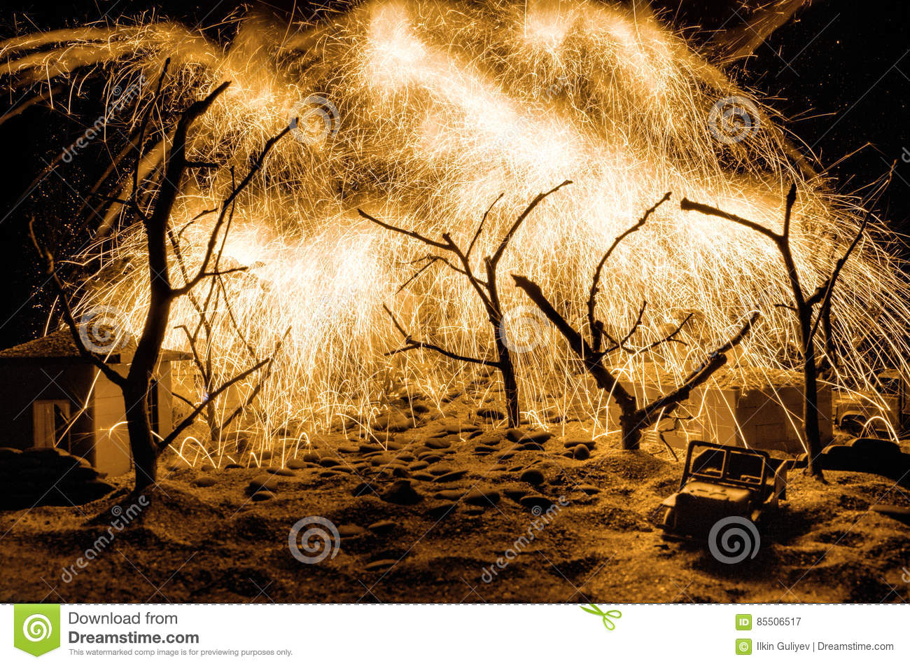 Forest Fire, Wildfire burning tree in red and orange color at night. On Table decoration with fireworks tree branches and sand
