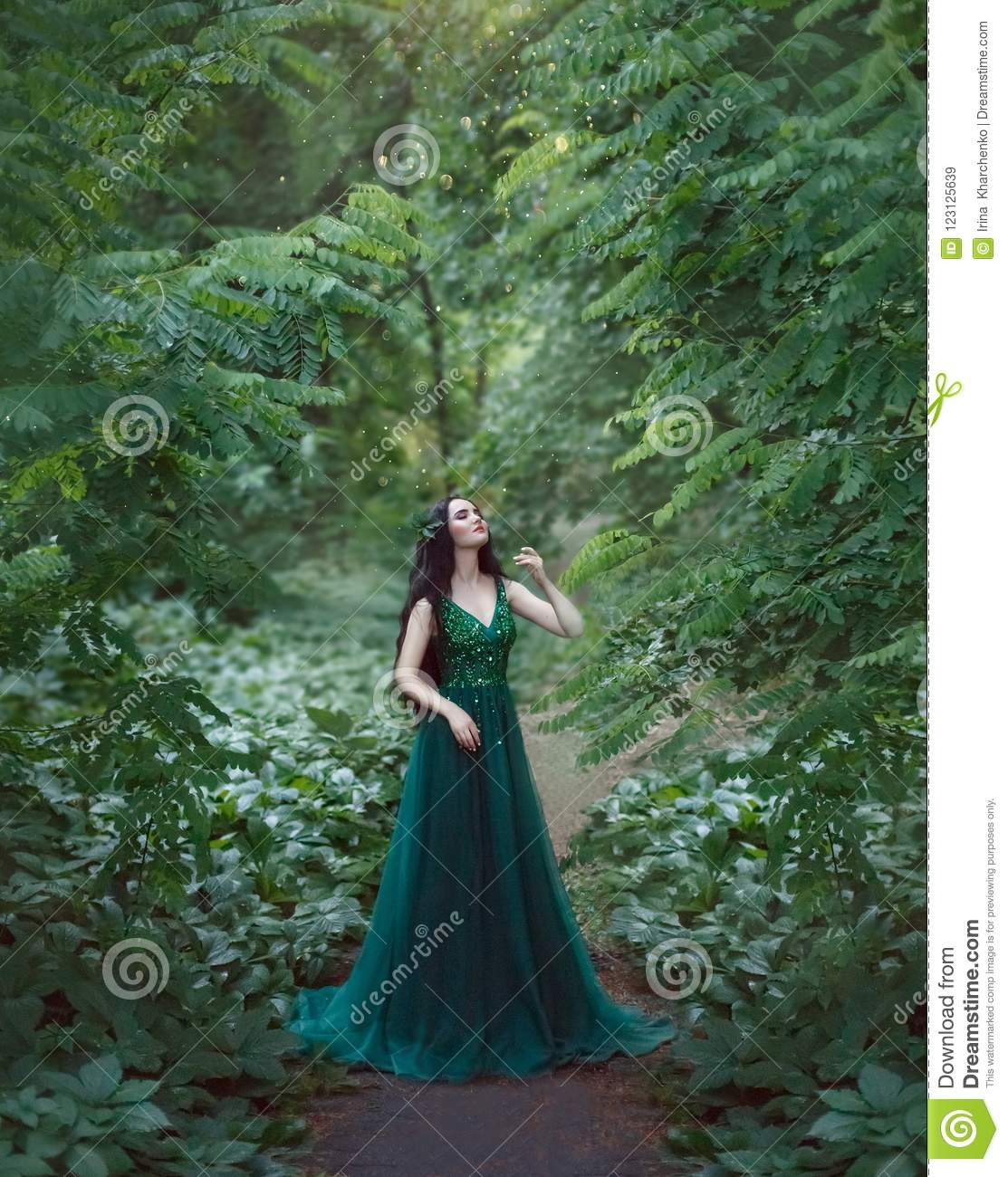 A forest nymph, a dryad in a luxurious, emerald dress, walks in the forest. Princess with healthy, long, black hair
