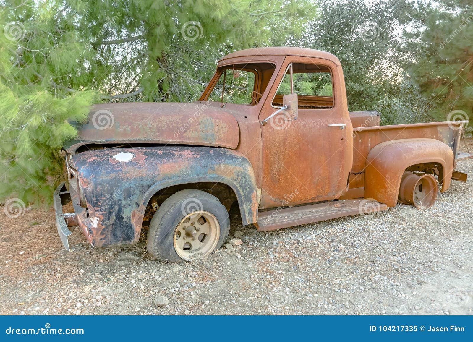Forest Relic Old Car que oxida afastado na floresta no cascalho