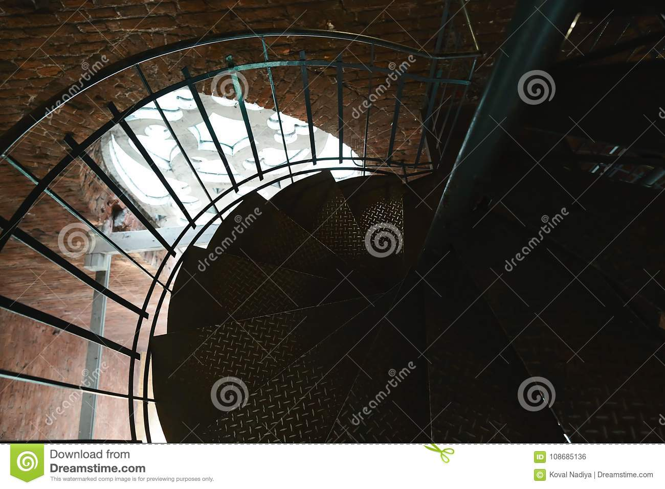 Forged iron twisted stairs with reflection on a red brick wall, handrails of the old vintage building, window with ornament