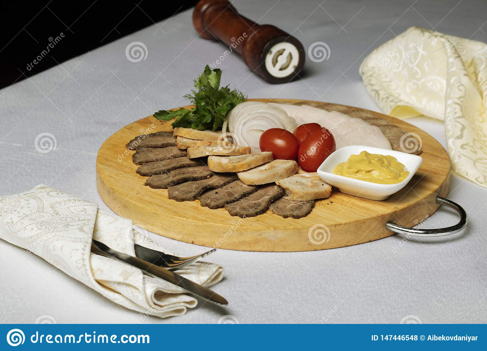 Fork and knife in napkin, Assorted meat, cheese sauce and cherry tomatoes with onion rings on textile