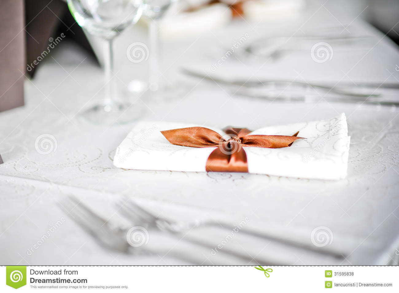 fork and spoon table decoration with ribbon over a white