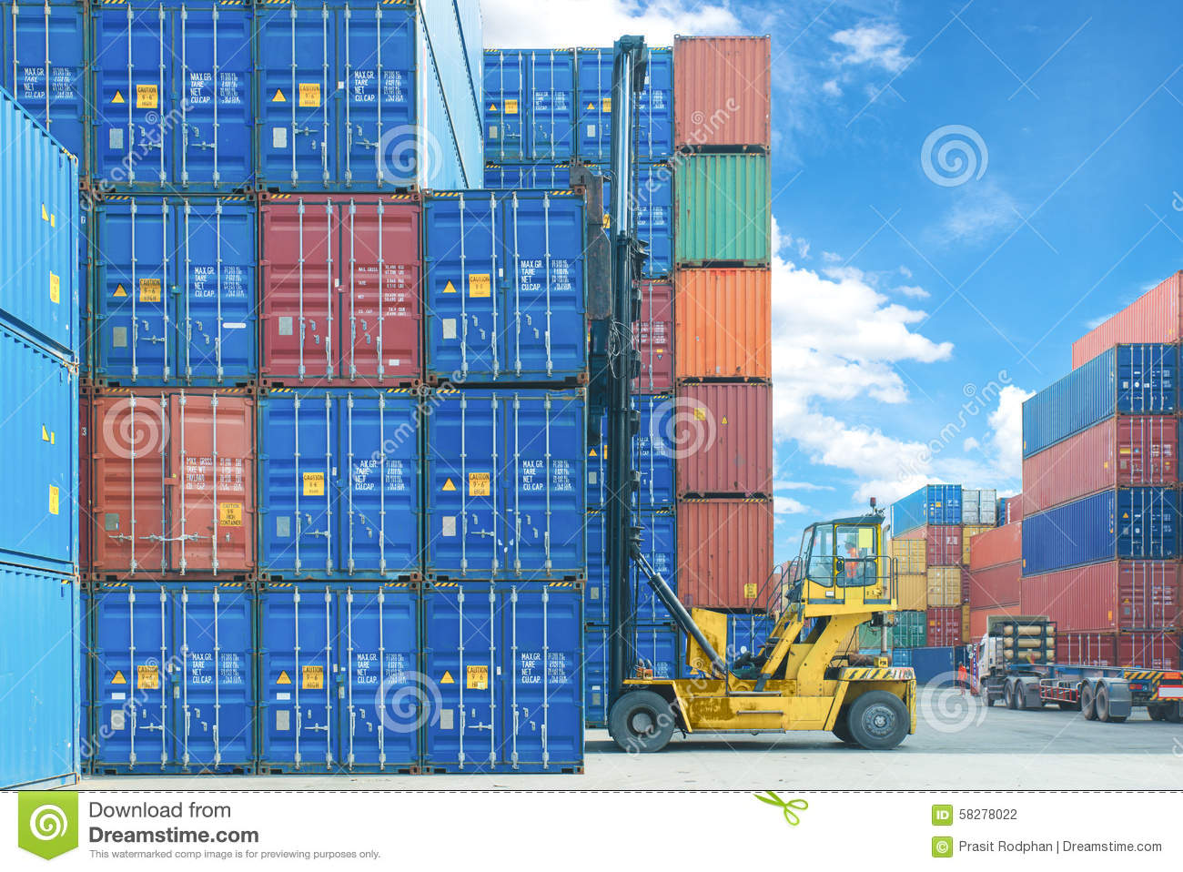 Forklift handling container box loading to truck in import export logistic zone.