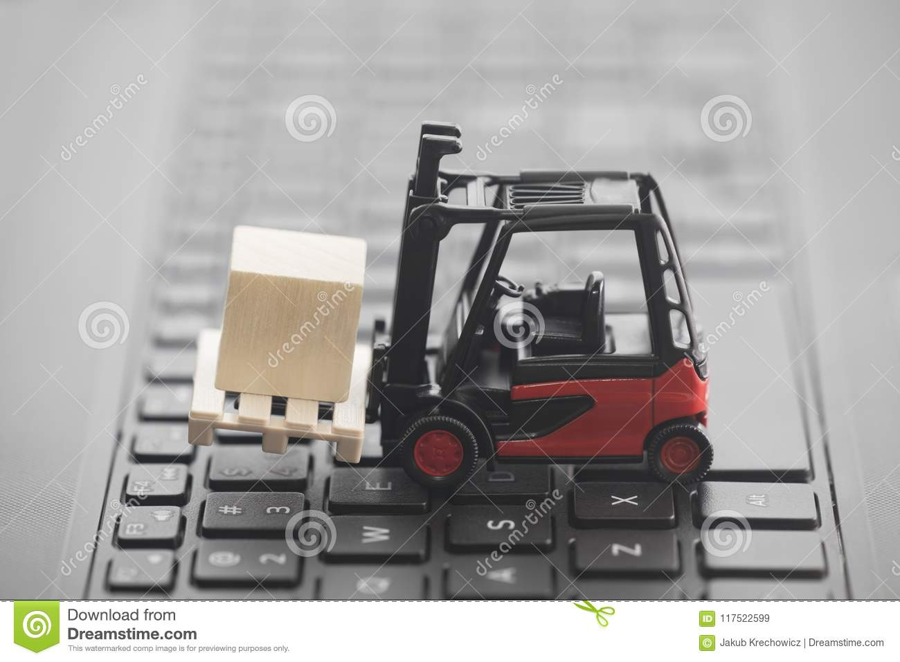 Forklift with wooden block on laptop keyboard