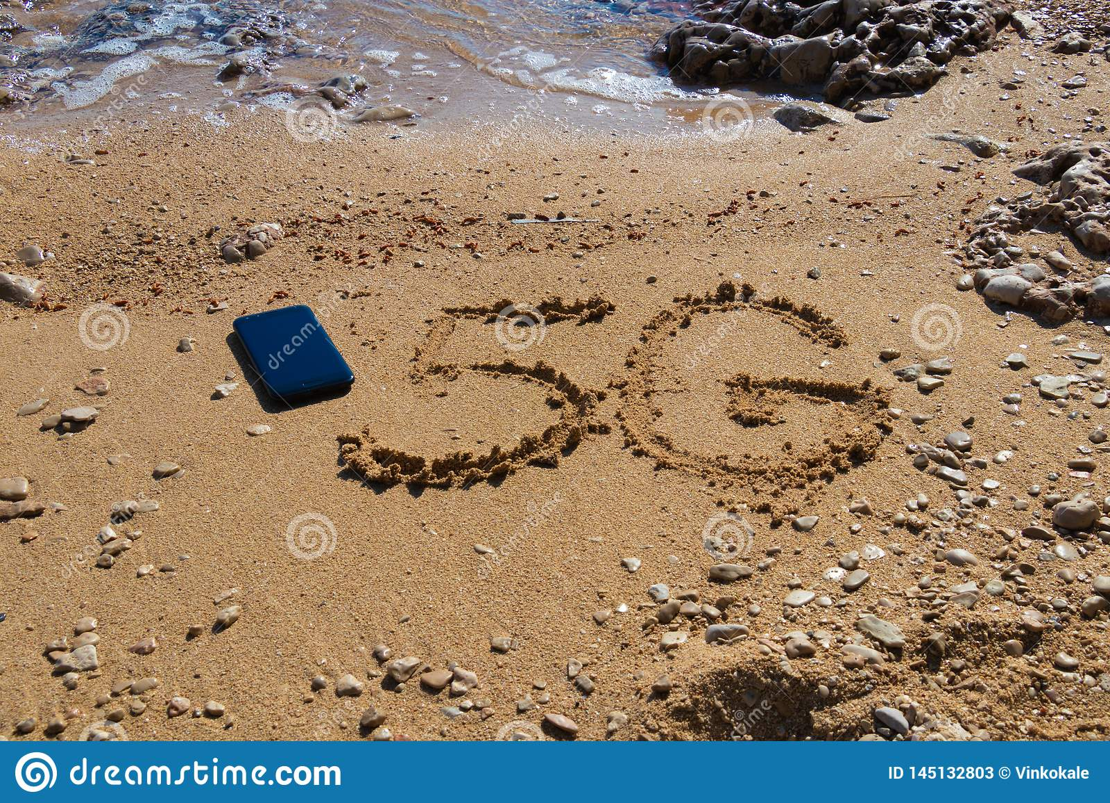 Form 5G auf dem Sand nahe Mobiltelefon
