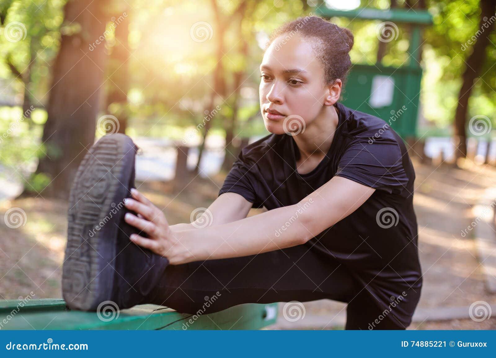 Formação ao ar livre Jovem mulher apta que estica seus pés