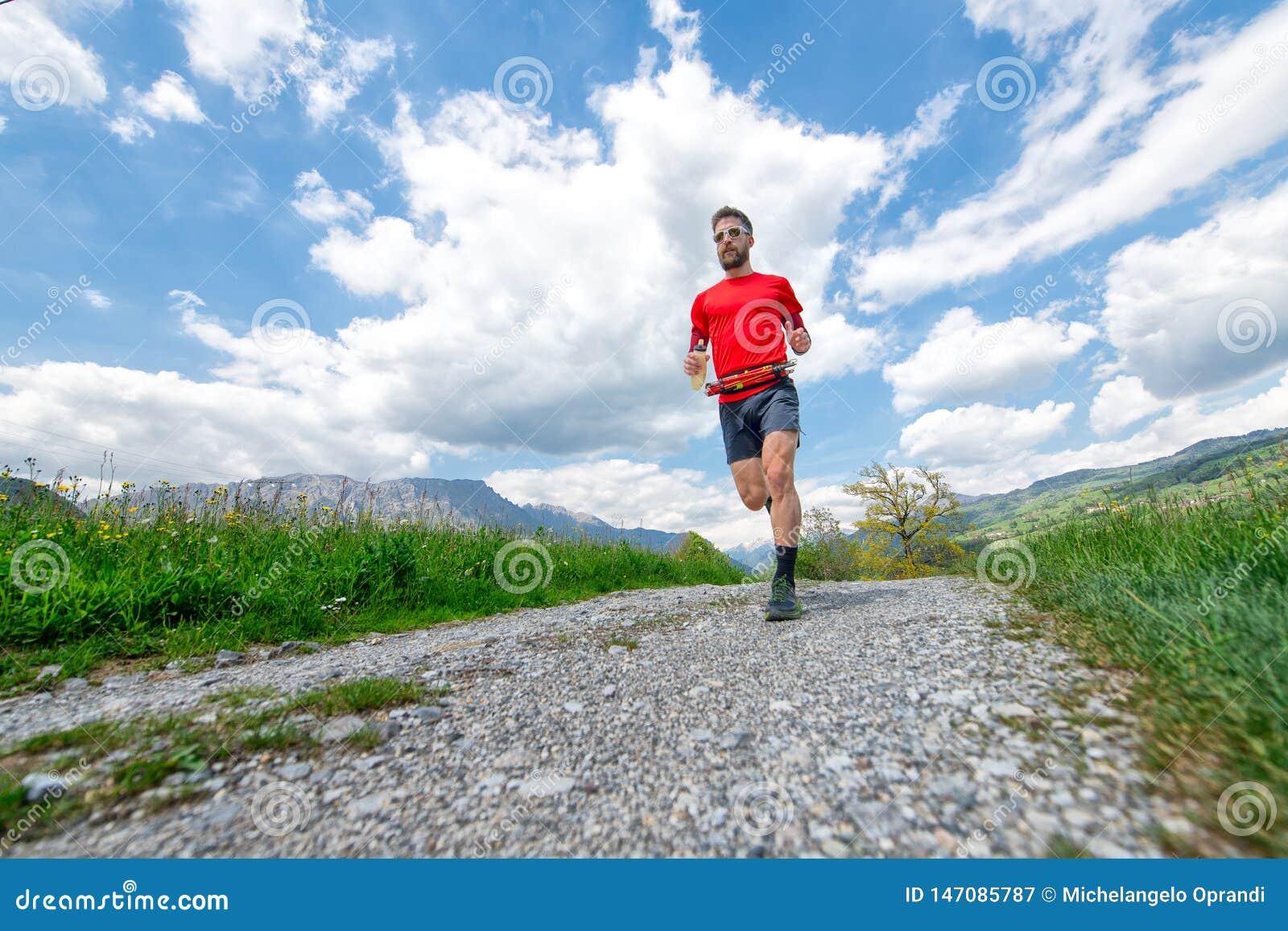 Formação de um corredor de maratona da montanha na estrada secundária