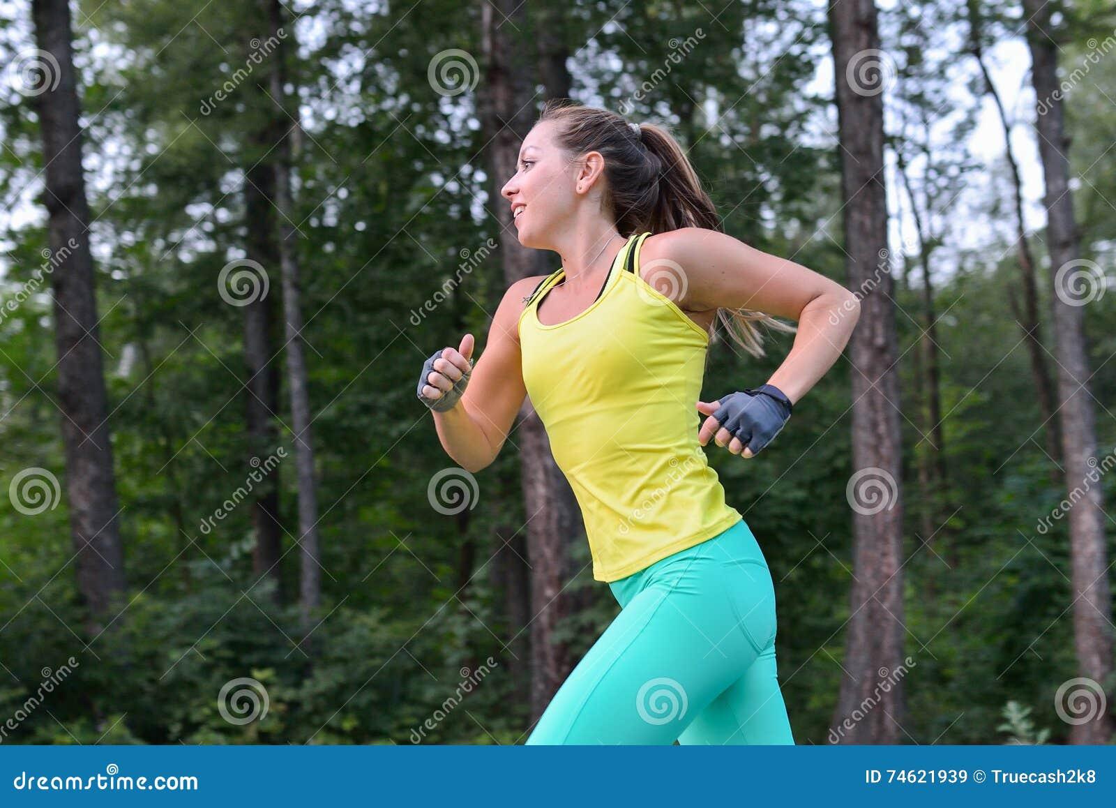 Formação fêmea do corredor exterior no perfil Imagem saudável do estilo de vida da jovem mulher que movimenta-se fora
