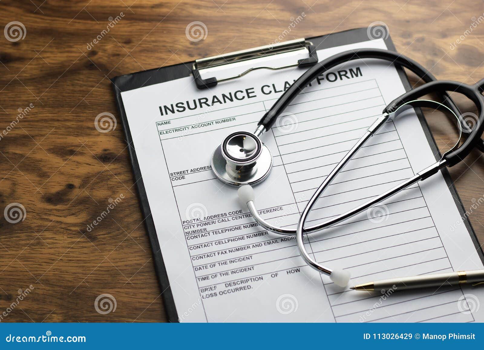 Forma de demanda del seguro médico con el estetoscopio en el selec de madera de la tabla