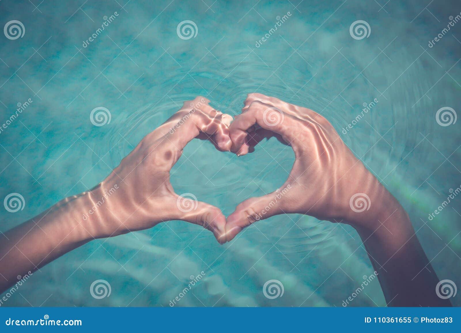 Forma de fatura fêmea do coração com mãos na água