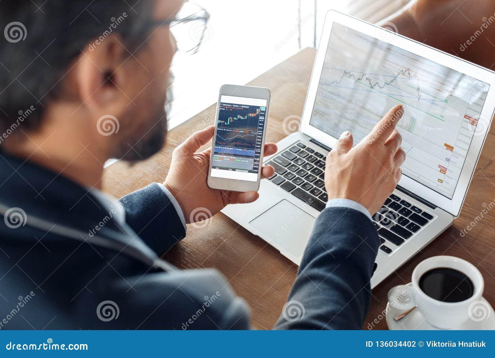 Forma de vida del negocio Comerciante que se sienta en el café con las cartas del comercio de la lectura del teléfono de la tenen
