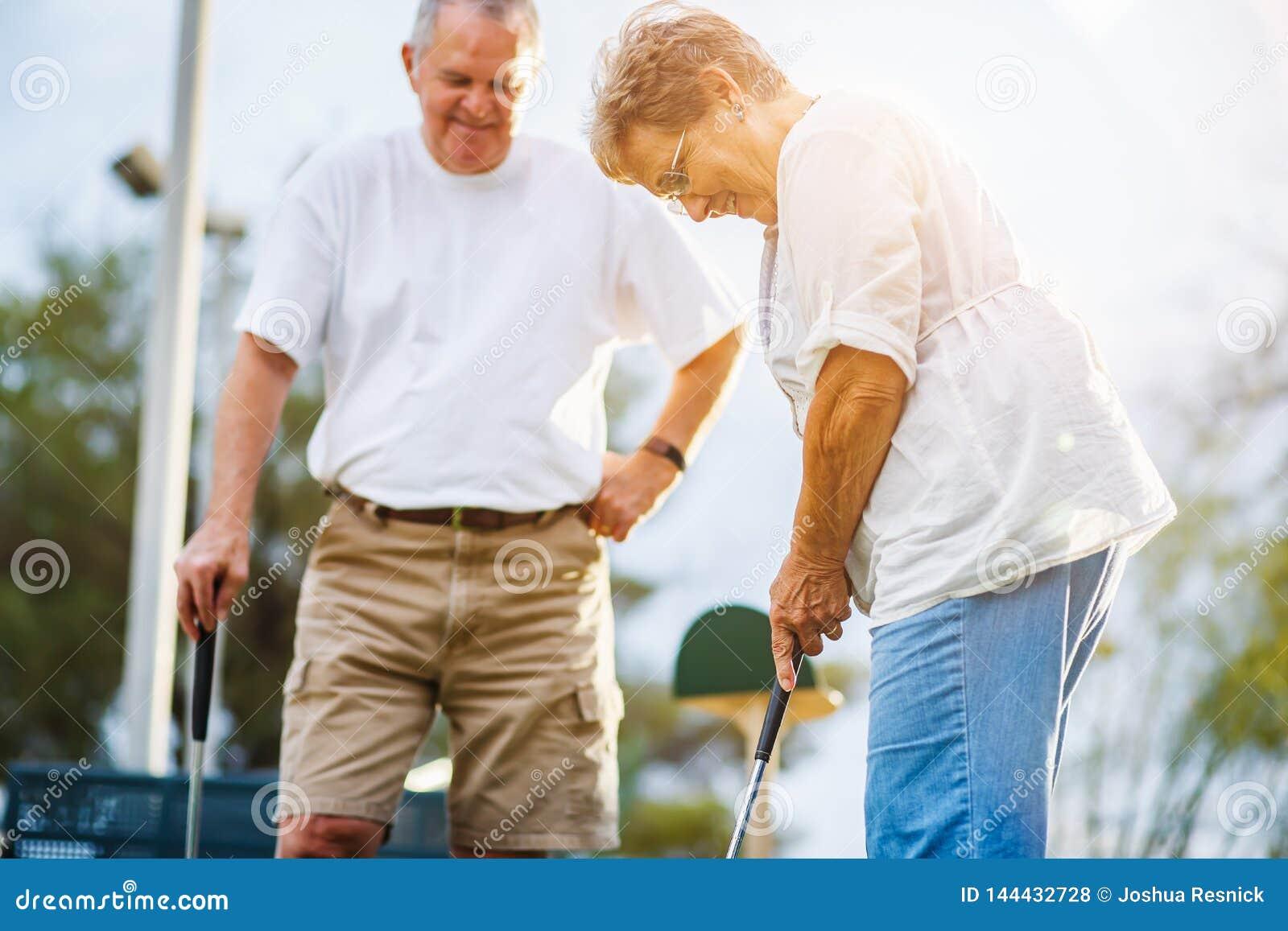 Forma de vida jubilada de los pares mayores que juegan a mini golf