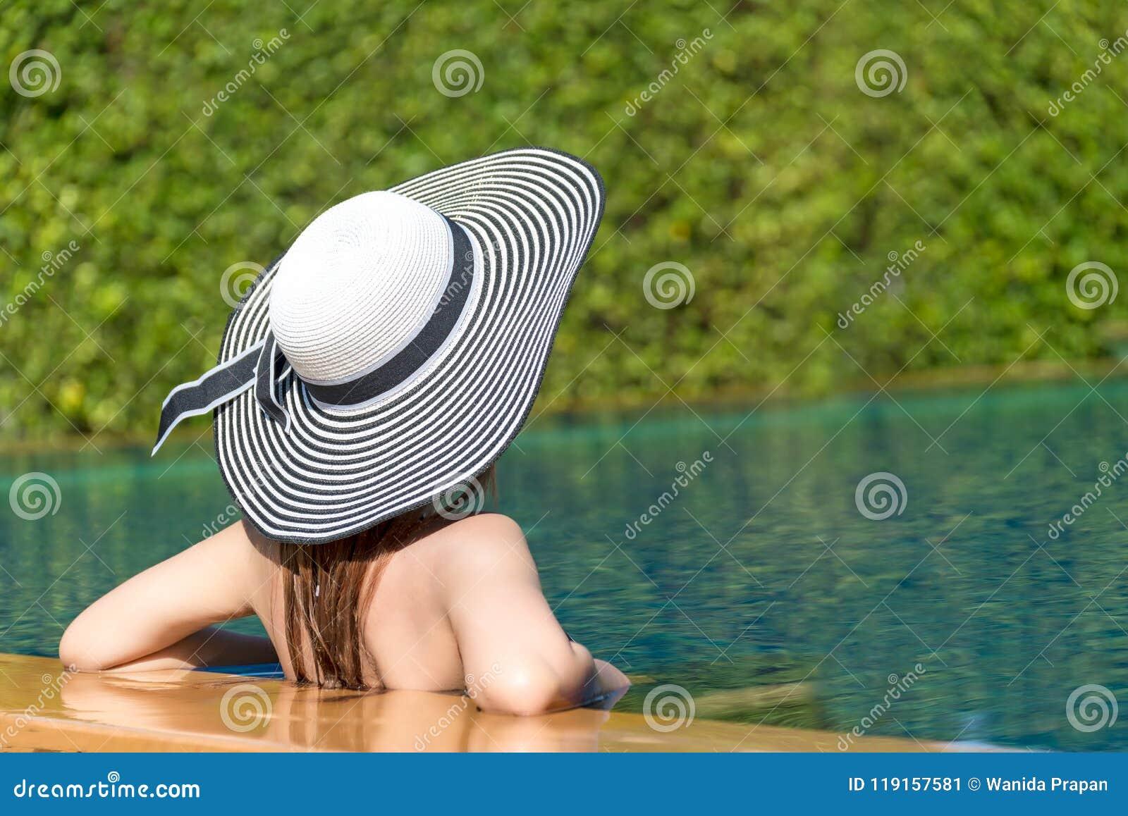 Forma de vida de la mujer joven tan feliz en el sombrero grande que se relaja en el lujo de la piscina