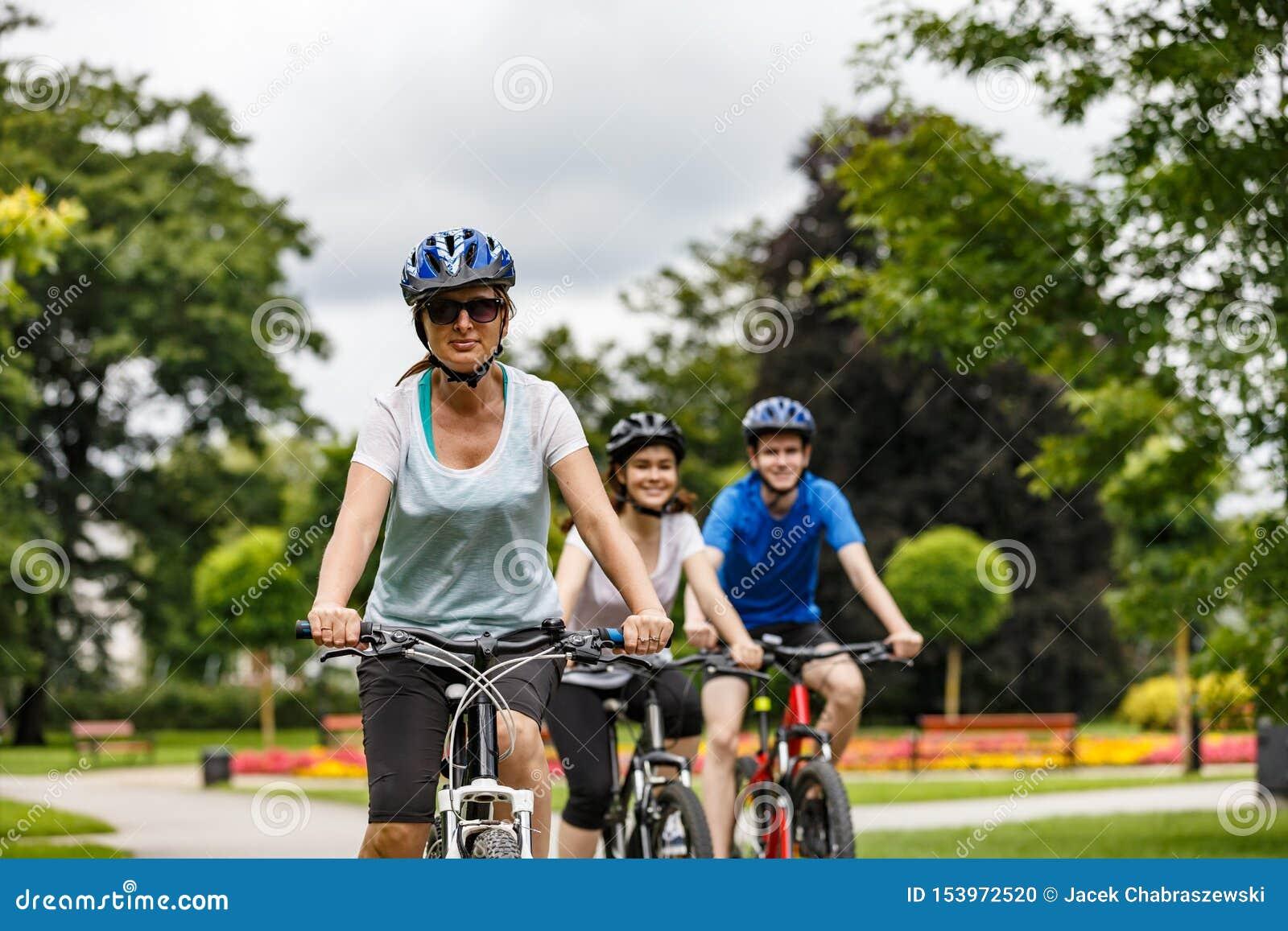 Forma de vida sana - bicicletas que montan de la gente en parque de la ciudad
