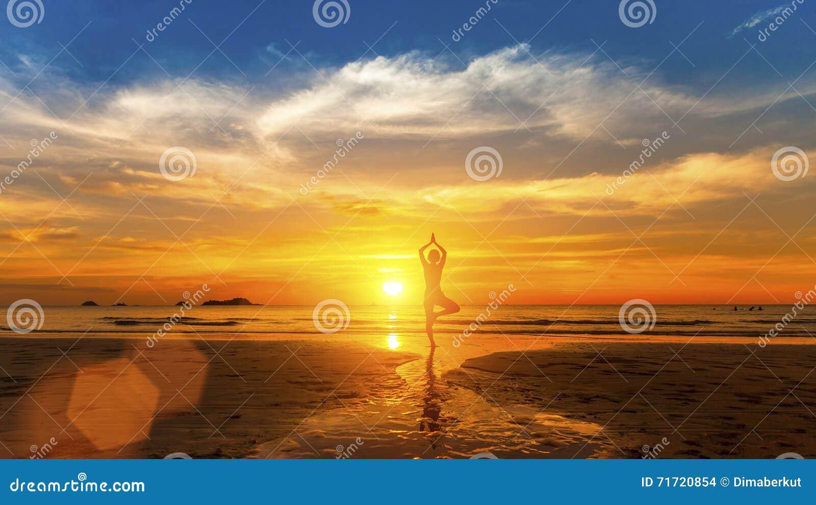 Forma de vida sana Siluetee a la mujer de la yoga de la meditación en el fondo del mar y de la puesta del sol