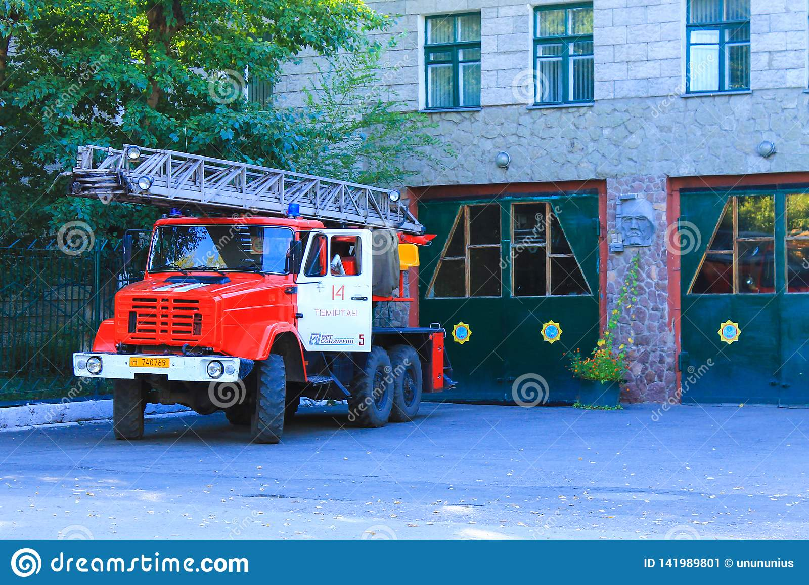 Forma de vida típica Kazajistán Edificio del cuerpo de bomberos central y del coche de bomberos rojo tradicional con la escalera