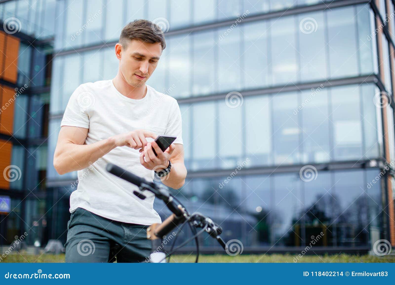 Forma de vida, transporte, comunicación y concepto de la gente - hombre joven con la bicicleta y smartphone en la calle de la ciu