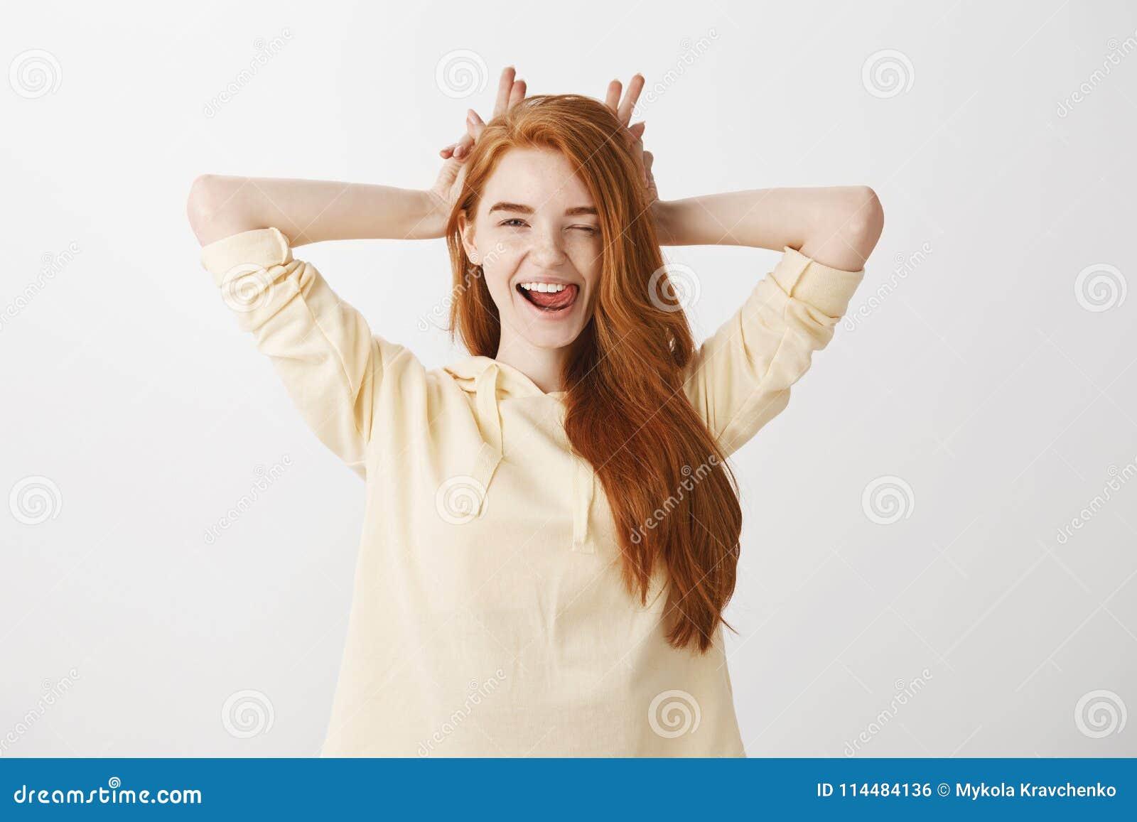 Forma de vida y concepto hermoso de la gente Tiro interior de la mujer elegante expresiva con el guiño rojo del pelo coqueto y so