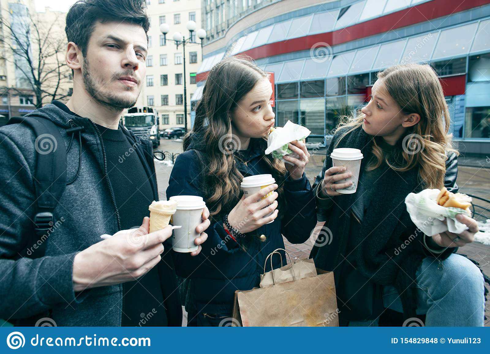 Forma de vida y concepto de la gente: dos muchachas e individuo que comen los alimentos de preparaci?n r?pida en la calle de la c