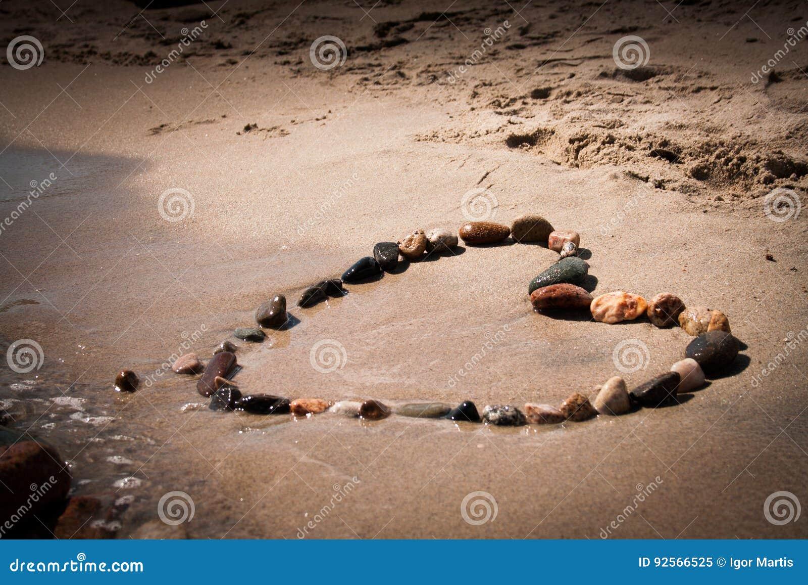 Forma del cuore con la pietra nella spiaggia