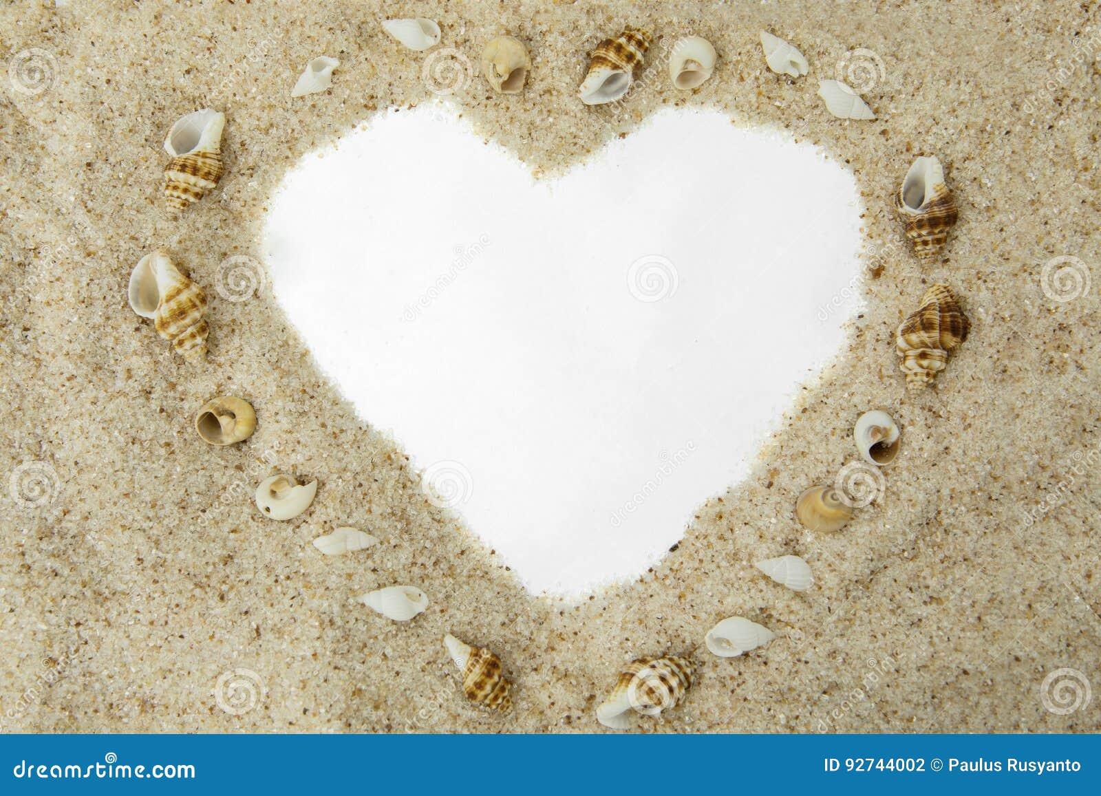 Forma del cuore sulla sabbia con le conchiglie